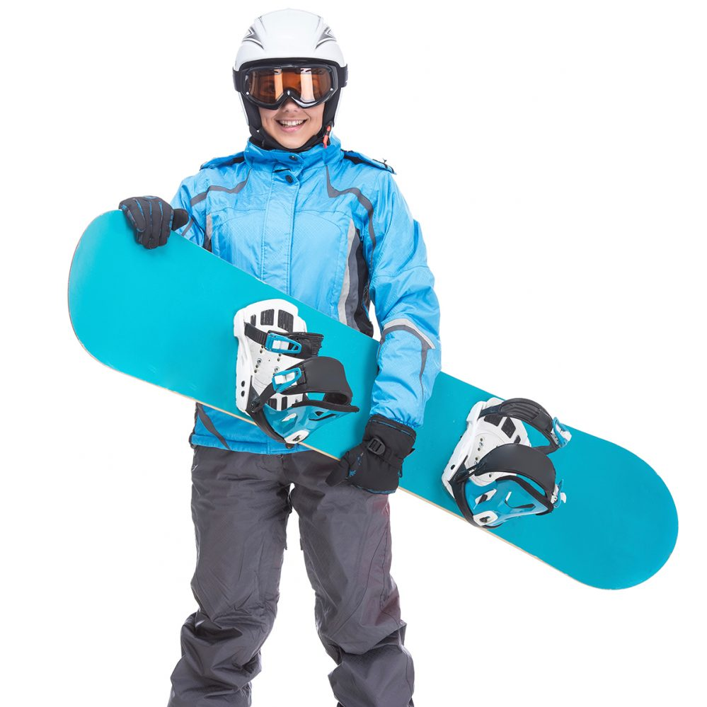 Young smiling woman is posing with snowboard and goggles in studio, isolated on white background.
